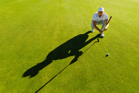 Golf player aiming shot with club on course. Male golfer check line for putting golf ball on green grass.