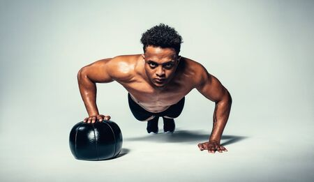 Horizontal shot of young fit man doing push up on medicine ball. Fitness male exercising with a medicine ball on grey background. Stock Photo