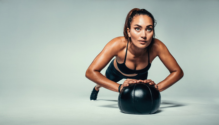 Horizontal shot of young fit woman doing push up on medicine ball. Fitness female exercising with a medicine ball on grey background. Reklamní fotografie