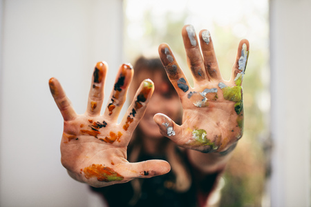 Close up of female artist showing her messy hands. Focus on hands of woman painter with color.