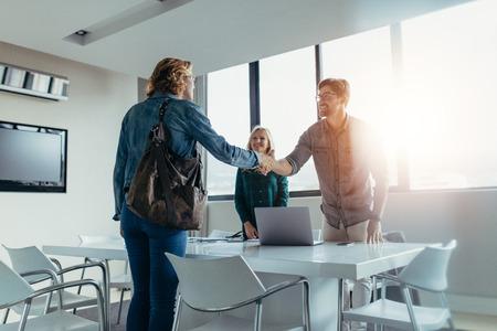 Bedrijfs mensen die een vergadering beëindigen. Man handen schudden met vrouwelijke klant na succesvolle deal. Stockfoto