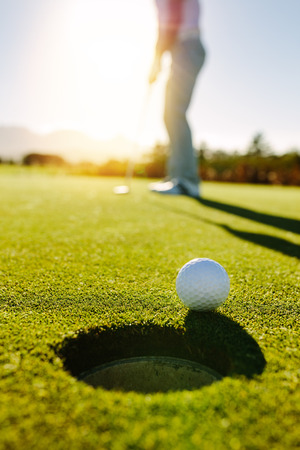 Golf ball at the edge of hole with player in background. Professional golfer putting ball into the hole on a sunny day.