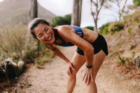 Fit young asian woman standing on mountain trail with her hands on knees and smiling. Female runner in sportswear taking a break after running workout.