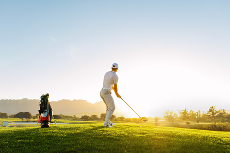 Full length of golf player playing golf on sunny day. Professional male golfer taking shot on golf course. Stock Photo