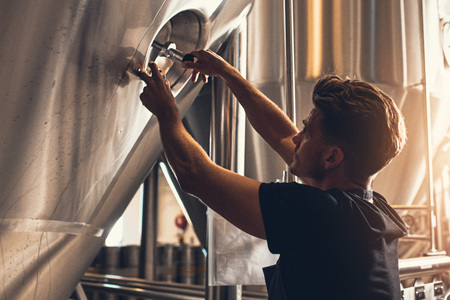 Brewer closing the hatch of brewery tank. Young male employee working in beer manufacturing factory. Stock Photo