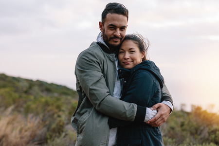 Portrait of a romantic couple hugging in countryside. Handsome young man embracing his asian girlfriend.