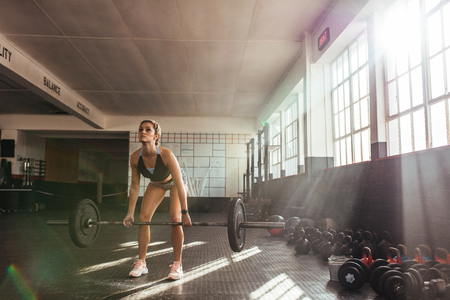 healthy body: Woman lifting heavy weights at the gym for muscle training. Athlete exercising using a weight bar.