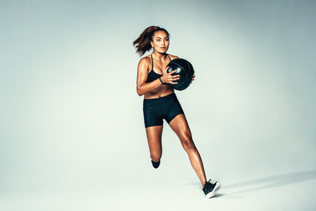 Studio shot of fit young woman running with medicine ball. Female model with muscular body working out with fitness ball over grey background.