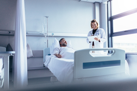 Female doctor talking to male patient in hospital bed. Smiling doctor with clipboard attending sick man in hospital ward.