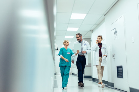 Group of medics with clipboard discussing along hospital corridor. Doctor and nurse briefing medical report with female colleague talking on mobile phone.