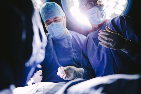 Medical professionals during surgery operating room. Group of surgeons in hospital operation theater. Stock Photo
