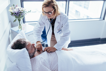 Doctor de la mujer que examina los latidos del corazón con el estetoscopio en un hombre hospitalizado. Médico asistiendo a un paciente masculino para un chequeo de rutina. Foto de archivo - 82811442