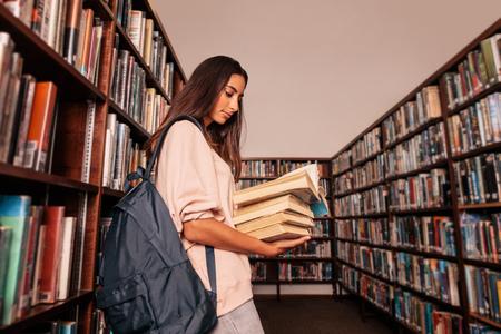 Jonge vrouwelijke student die veel boeken in de universiteitsbibliotheek draagt. Kaukasische studentenlezingsboeken in bibliotheek. Stockfoto - 82755429