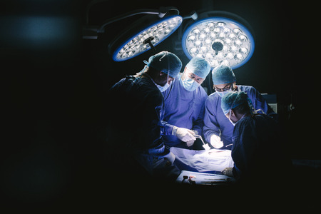 Group of surgeons in hospital operating theater. Medical team performing surgery in operation room.