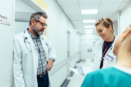 Arts met collega's in ziekenhuishal. Ziekenhuispersoneel werkt en kijkt naar medische rapporten.