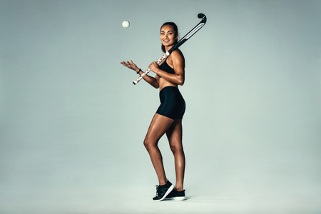 Full length portrait of happy young woman holding hockey stick and ball over grey background. Hispanic female hockey player smiling.