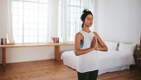 Retrato de joven mujer sana de pie con las manos unidas y los ojos cerrados en casa. Fitness mujer meditando en el interior. Foto de archivo - 82752044