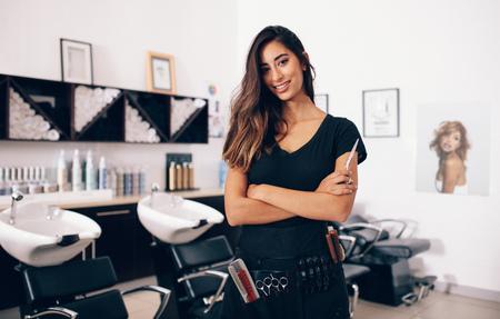 はさみを手に保持しているサロンで女性美容師。笑顔の若い美容師サロンに立っています。