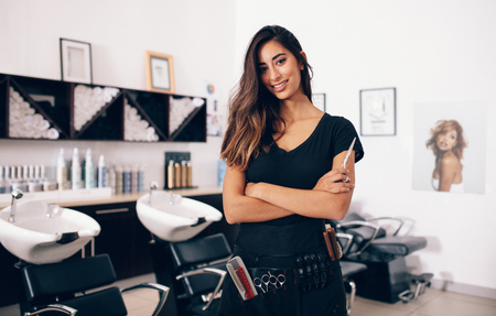 woman mirror: Female hairdresser in salon holding scissors in hand. Smiling young hairdresser standing in salon. Stock Photo