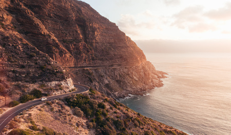 Car driving along Chapmans Peak Drive in South Africa. Epic road along the mountains.