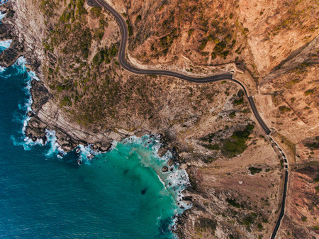 Aerial view of road going through beautiful landscape. Rocky scenery close to the ocean. Stock Photo