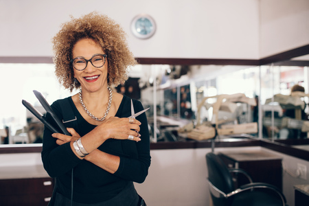 Professional hair stylist holding a hair straightener and scissors. Woman hairdresser in happy mood at the salon. Zdjęcie Seryjne
