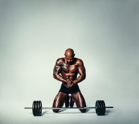 Studio shot of fit african man with barbell. Muscular young man working out with heavy weights over grey background. Banco de Imagens