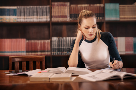 College student preparing for the exam in library. University student taking notes from book while sitting in library. Stok Fotoğraf