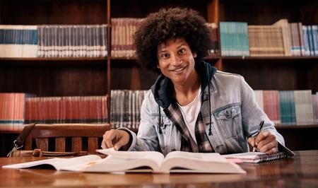 Jonge zelfverzekerde student leren van boeken in de bibliotheek. Universitaire student die in de bibliotheek bestudeert. Stockfoto - 83060161
