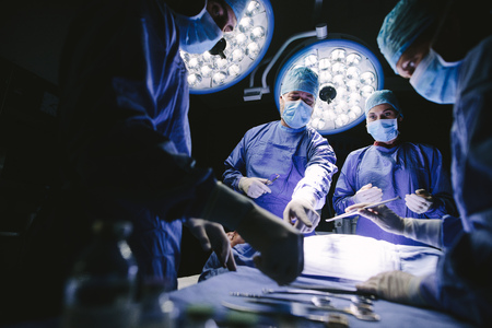 suite: Group of surgeons in operating theater. Medical team performing surgery in operation room.