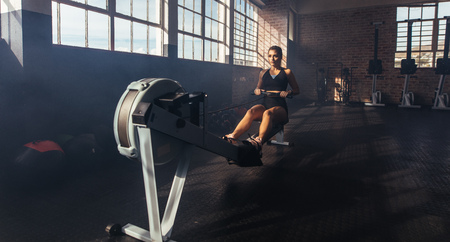 Athletic young woman exercising on training apparatus at the gym. Woman strengthening her muscles by pulling weight at the gym.