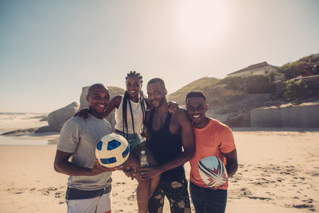 Young friends standing together on beach with american football and soccer ball. Group of friends on summer beach vacation.