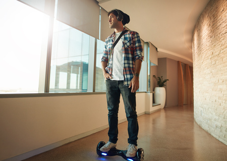 Indoor shot of young man riding on self-balancing electric scooter in office. Creative professional on hover board. Stock Photo