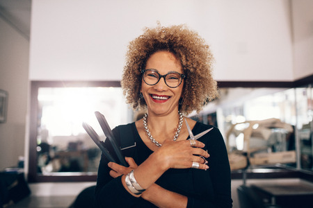 Hairdresser holding a hair straightener and scissors. Closeup of curly haired woman hairdresser in happy mood at the salon. Zdjęcie Seryjne