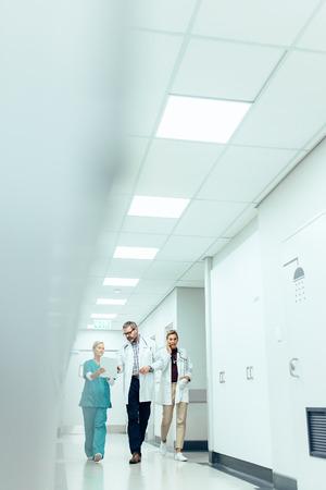 병원 복도를 따라 걷는 동안 작업을 논의하는 의료 팀. 복도에서 브리핑 브리핑의 수직 이미지.