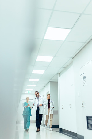 Medical team discussing work while walking along the hospital corridor. Vertical image of medics briefing in hallway.