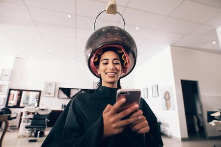 그녀의 머리에 롤러와 머리 주위 김이 기계 스파에서 여자. 김이 머리를 겪고있는 동안 미용실에서 휴대 전화를 찾고 웃는 여자. 스톡 콘텐츠