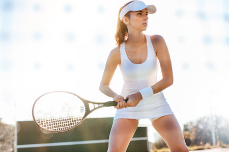 Female tennis player playing match on court. Sports woman with racket playing on tennis court.