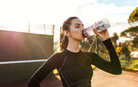 Portrait of beautiful young woman drinking water after workout on a sunny day. Sportswoman taking break after training session on tennis court.