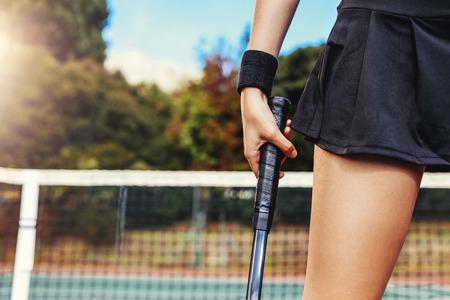 Close up of female player hand holding tennis racket on court. Cropped shot of woman holding a tennis racket at the court.