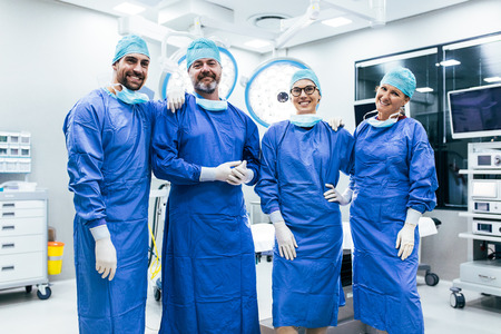 suite: Portrait of successful medical workers in surgical uniform in operation theater. Team of surgeon standing in operating room, ready for next operation.