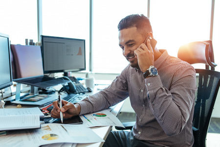 Businessman talking on mobile phone and looking down with smile pointing at business papers. Man sitting at his office desk working on graphs and charts and discussing on phone.