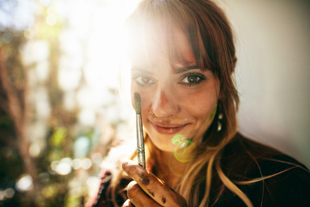 Close up shot of beautiful young woman holding brush with sunflare. Face of female painter looking at camera.