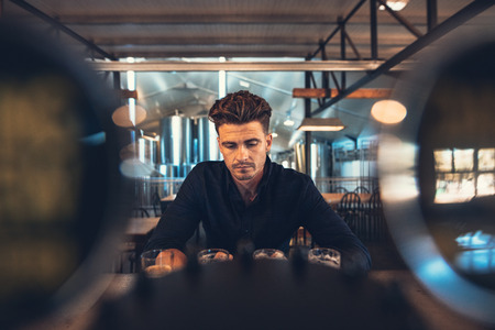 Young man sitting at brewery tasting room with different types of beers. Brewer tasting varieties of craft beers at brewery. Фото со стока