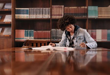 Jonge student schrijven van notities uit boek in de bibliotheek. Universitaire student die taak in bibliotheek doet. Stockfoto
