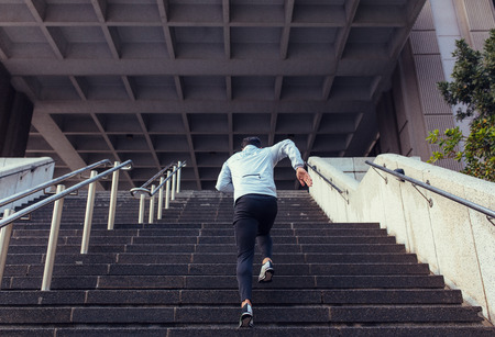 Man running up the stairs of a building. Athlete climbing stairs as part of his physical training. Reklamní fotografie