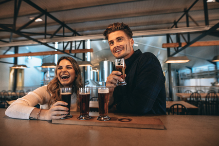 Smiling young couple at the bar with different varieties of craft beers. They are at brewery and tasting beers. Фото со стока
