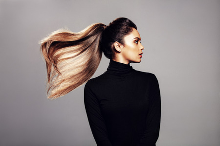 Studio shot of stylish young woman with flying hair against grey background. Female fashion model with long hair. Foto de archivo