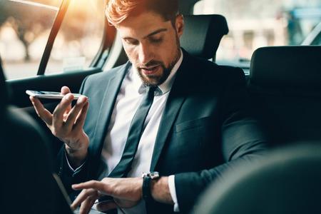 apuesto hombre de negocios hablando por teléfono mientras está sentado en el asiento de la joven del hombre de negocios con el coche portátil usando teléfono inteligente y enviar tiempo