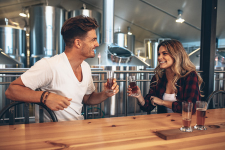 Couple at brewery toasting beers. Young man and woman tasting different varieties of craft beers. Archivio Fotografico